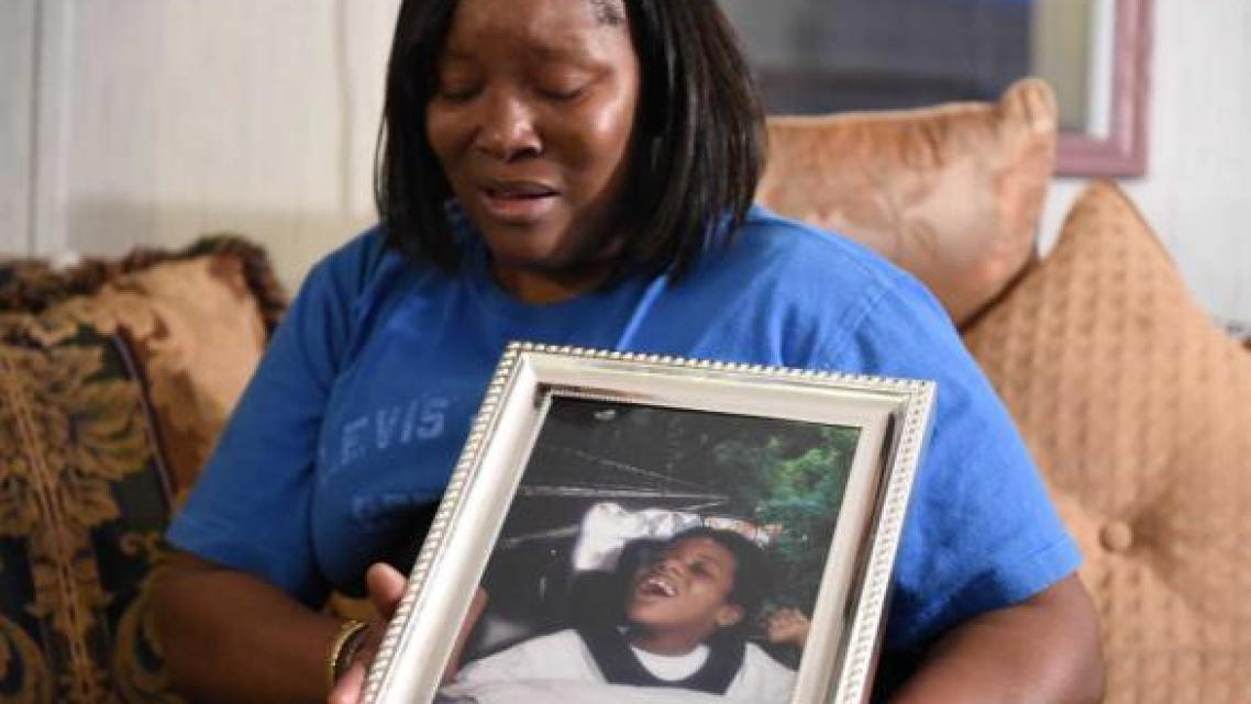 Jessie Evans becomes emotional as she holds a portrait of her son, Cornelius James Evans, taken when he was 5 years old, at her home in Donalsonville, Ga. JON-MICHAEL SULLIVAN/STAFF