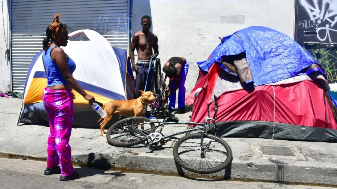 Homeless residents chat beside their tents on a street in downtown Los Angeles, California on June 25, 2018.