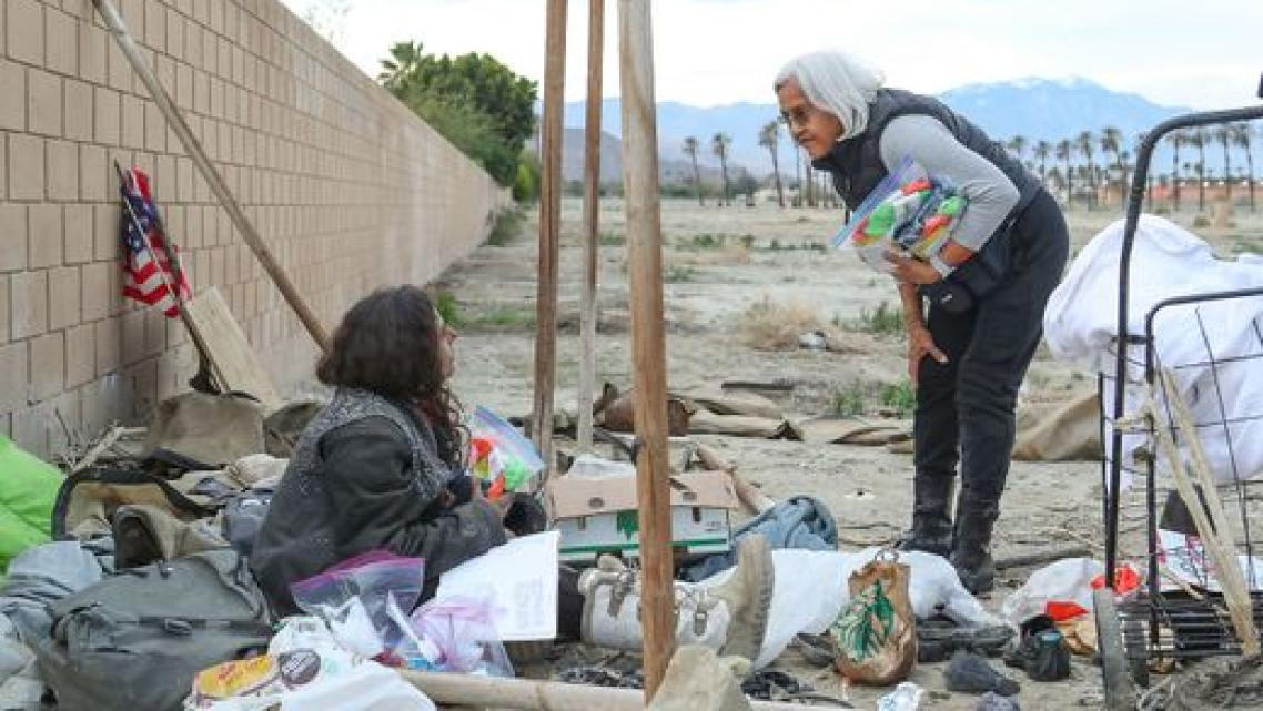 Terry Ramon, right, talks with a young homeless woman in Indio.