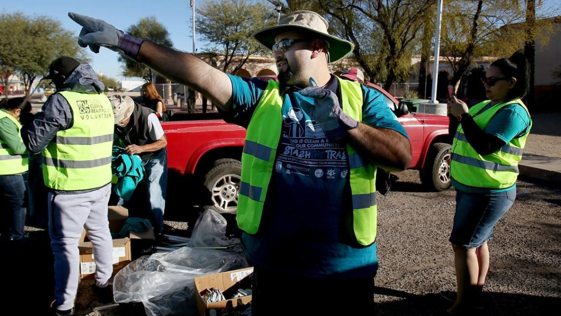 Lorenzo Gonzalez, head of the Healthy South Tucson Coalition, directs a trash cleanup on South Sixth Avenue, an area of concentr