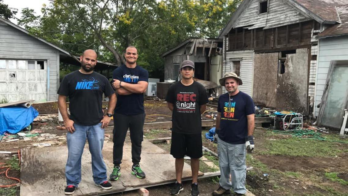 Amilcar Heredia, Eduardo Assef, Robert Santos and Isaac Fonseca stand outside Reynaldo Garza's home after cleaning up debris in