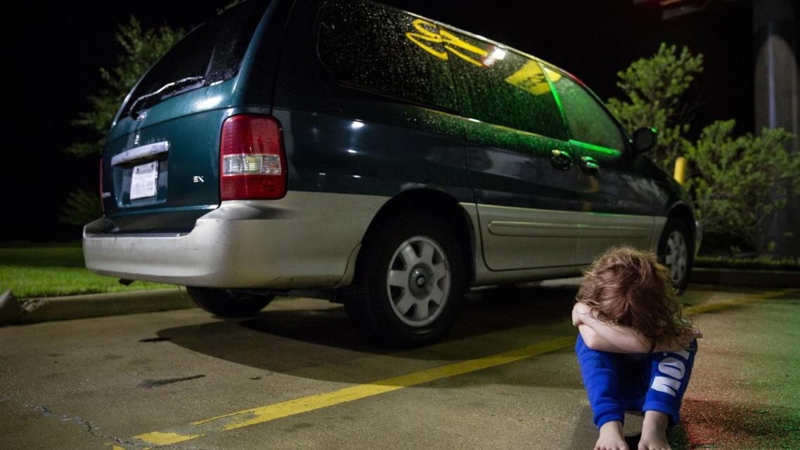 In a Victoria motel parking lot, Zoey Bowman sits on the ground and pouts in front of her mother's minivan in September.