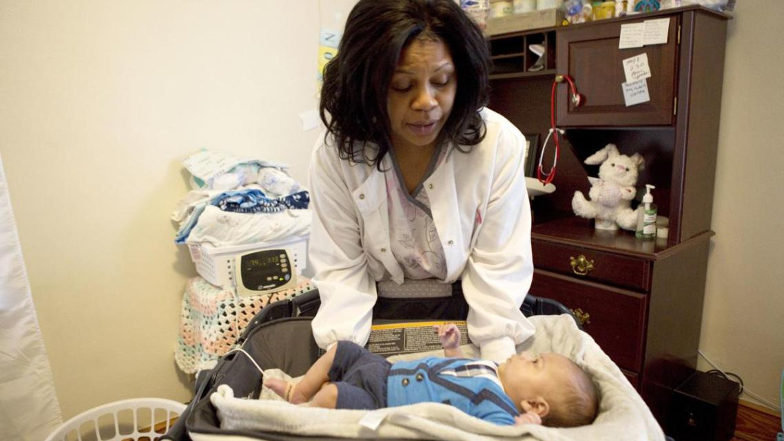 Flossie Horace takes oxygen levels and weighs her 3-month-old grandson every morning in her Roanoke home.