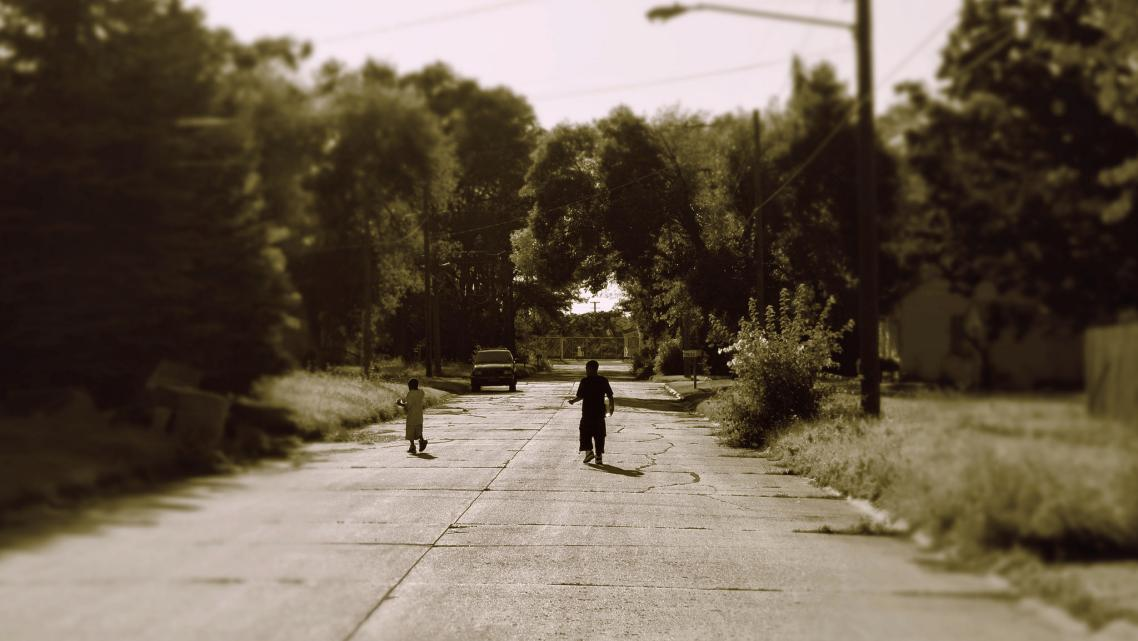 two children walking in the street between trees