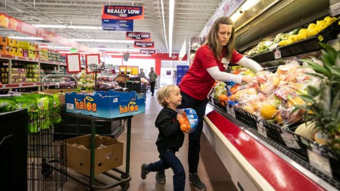 Jenny Kute and four-year-old son Henry put out fresh produce at the family's Save-A-Lot on Taylor Boulevard in the Hazelwood nei