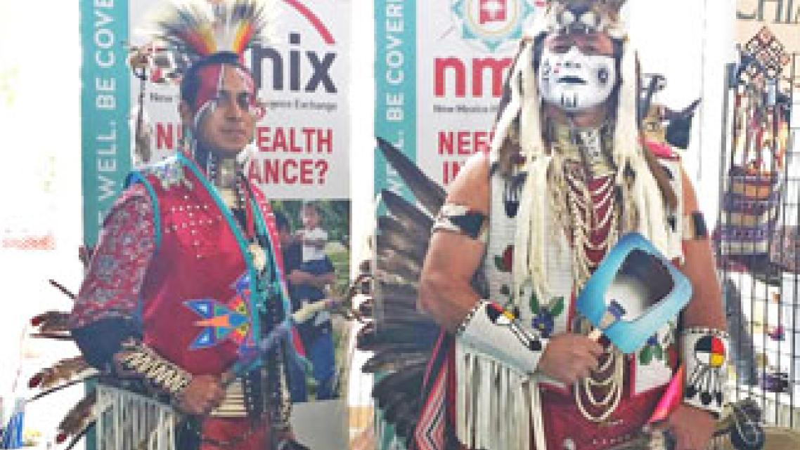 Two dancers in regalia work a Native American Professional Parent Resources outreach booth at the 2014 Gathering of Nations powwow in Albuquerque, N.M. | Courtesy Photo