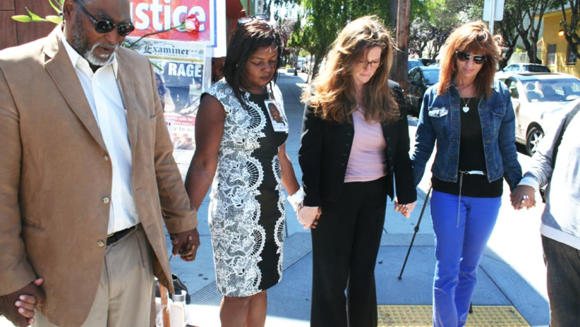 George Jurand and Paulette Brown accompanied by friends and SFPD agents, pray for Aubrey abraska on the corner of Grove and Baker streets on Aug. 14, seven years after Abraska was murdered. Photo Francisco Barradas
