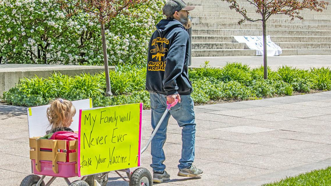 """A man pulls a wagon at an """"Open Ohio"""" protest rally in front of the statehouse this spring."""