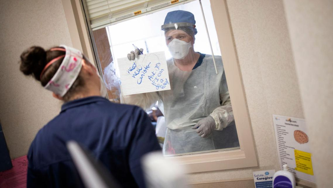 Nurses in the intensive care unit of MedStar St. Mary's Hospital communicate through a window with an erasable whiteboard from a