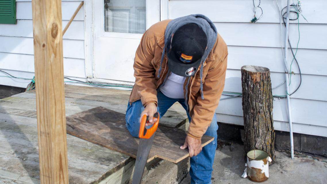 Luis, not his real name, cuts wood to repair a section of flooring in his Mt. Pleasant, Iowa home on Monday, February 3, 2020.