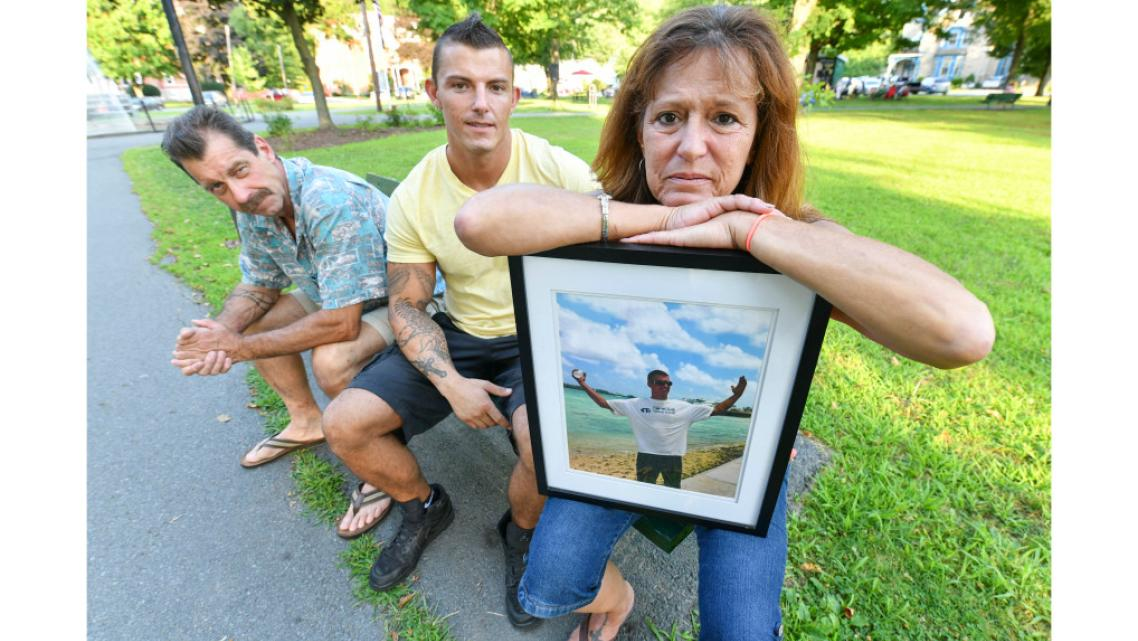 Lynne Russell, of Hawley Pa., holds a photo of her late son, Patrick, on July 25, 2019, as she sits with her husband Patrick.