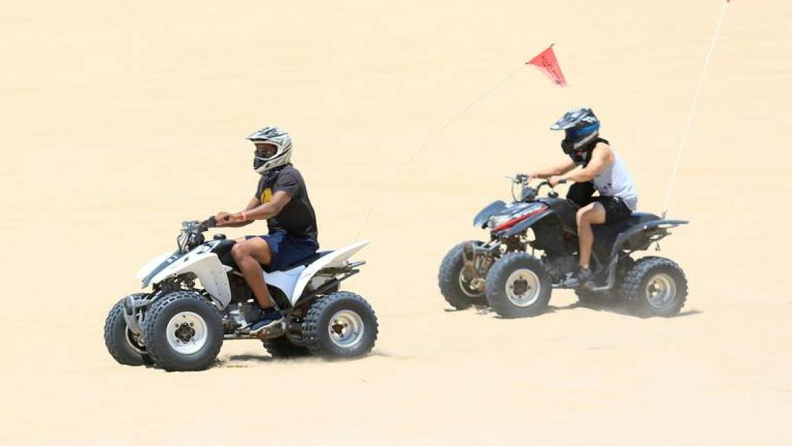 Two riders on quads ride in the OHV area of Oceano Dunes in June. Laura Dickinson