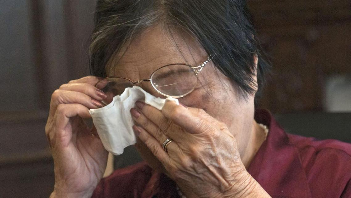 Tri Minh Le, 82, of Westminster, tearfully recalls her late husband.
