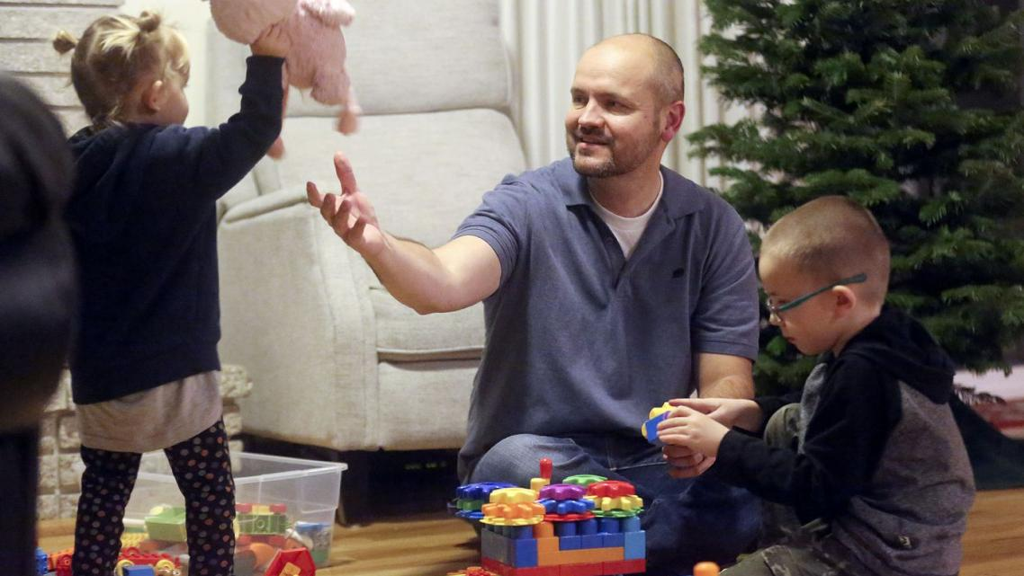 Dustin Wallis, a nonsmoker who has stage 4 lung cancer, plays with his children in Cottonwood Heights, Utah.