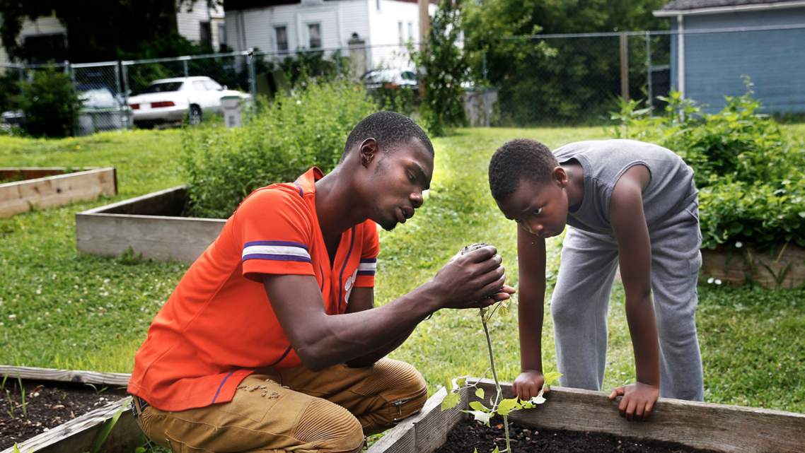 """Nate Collins, 19, left, helps Deonta Williams, 9, prepare to plant a tomato plant on a Saturday in July at """"We Got This,"""" a prog"""