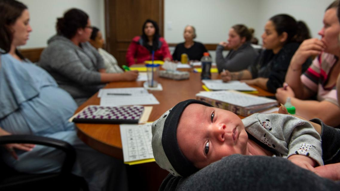 One-month-old baby Alexander rests in his mother's arms during a group therapy session for women and mothers dealing with substa