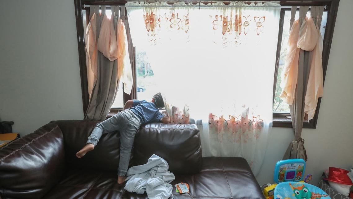 Jace Jarrett, 4, stands on his family's large couch and peers out the window waiting for his father to come home from work on a
