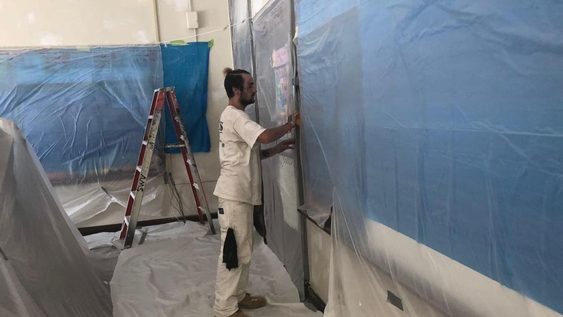 A worker performs lead paint and plaster stabilization at Clara Barton Elementary School.