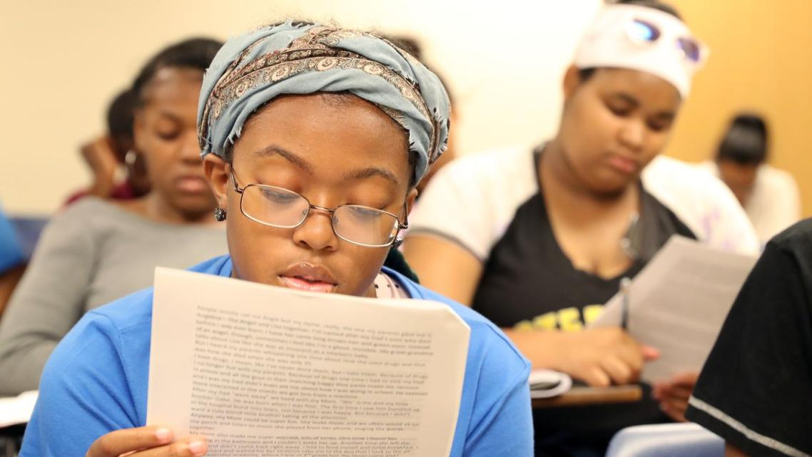 Cailah Porter, 15, reads over an example of a short story as she and fellow Upward Bound students prepare to work in groups to c