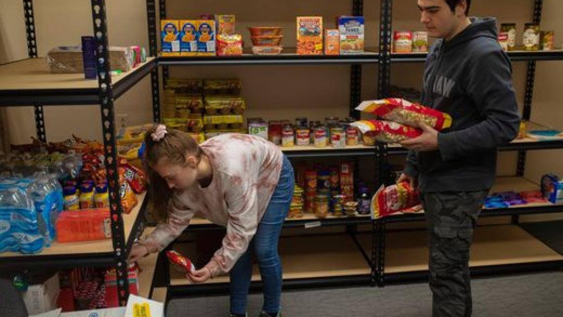 Bellarmine students stow away food items picked up at the Dare to Care food bank to be added to the university's food pantry. Th