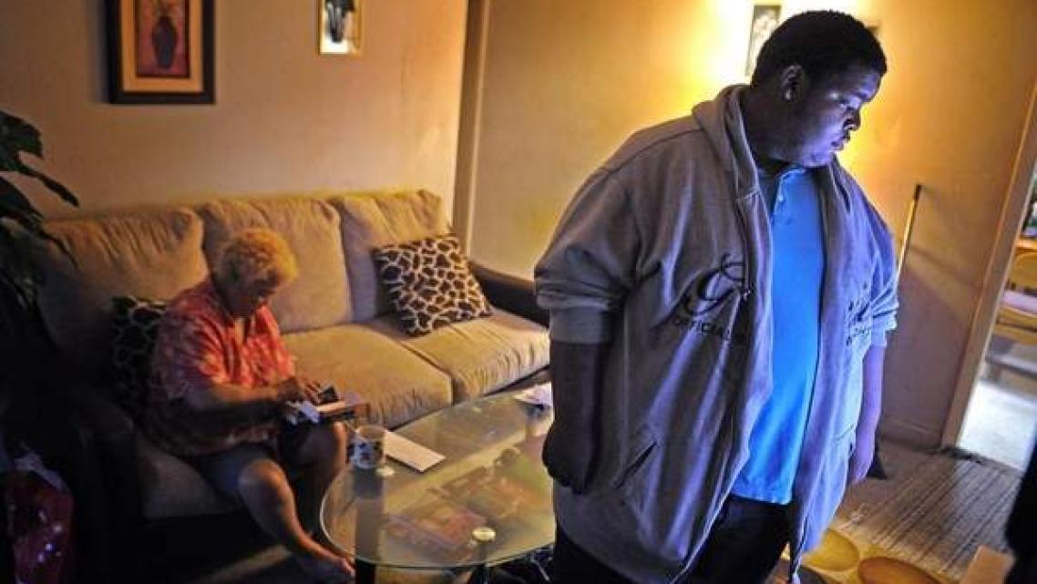 Deonta Ridley watches TV while his grandmother, Nellie Diaz, fishes around in her purse for money so he can go to the store to get them a snack. Diaz has diabetes, and Deonta learned last year that he has elevated cholesterol and is at risk for developing diabetes. / Larry McCormack / The Tennessean