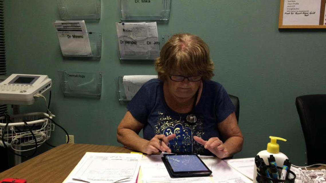Donna Armes, director of The Haley Center in Winter Haven works on a patient's chart.