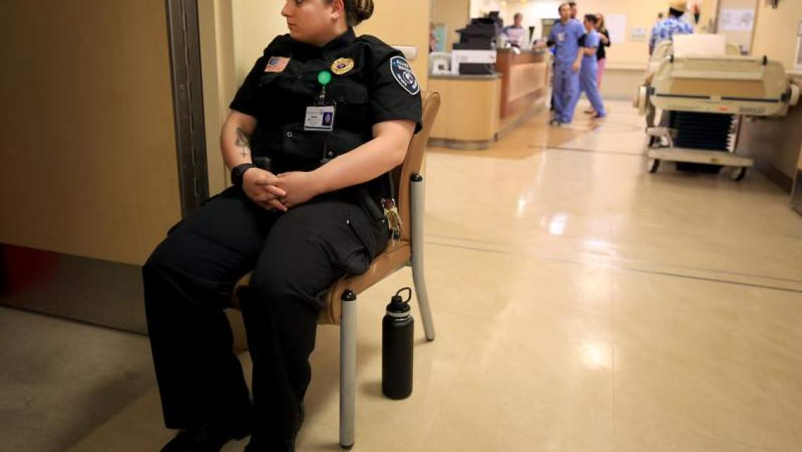 Hazel Brownfield Rosalie of Allied Universal Security keeps watch on a mental health patient in the emergency room.