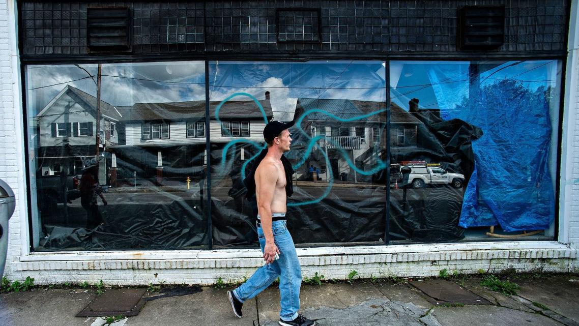 Travis Litts walks past an abandoned business along East Ridge Street in Lansford. He is one of Pennsylvania's many rural reside