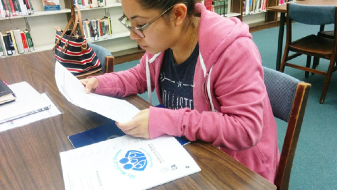 DACA recipient Stephanie Martinez reviews the Medi-Cal documents she received by mail. (EGP photo by Jacqueline Garcia)