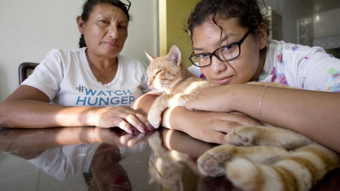 Orange Chicken the cat enjoys the late afternoon sun with his owner Carolina Torres and her mother Margarita Montes.