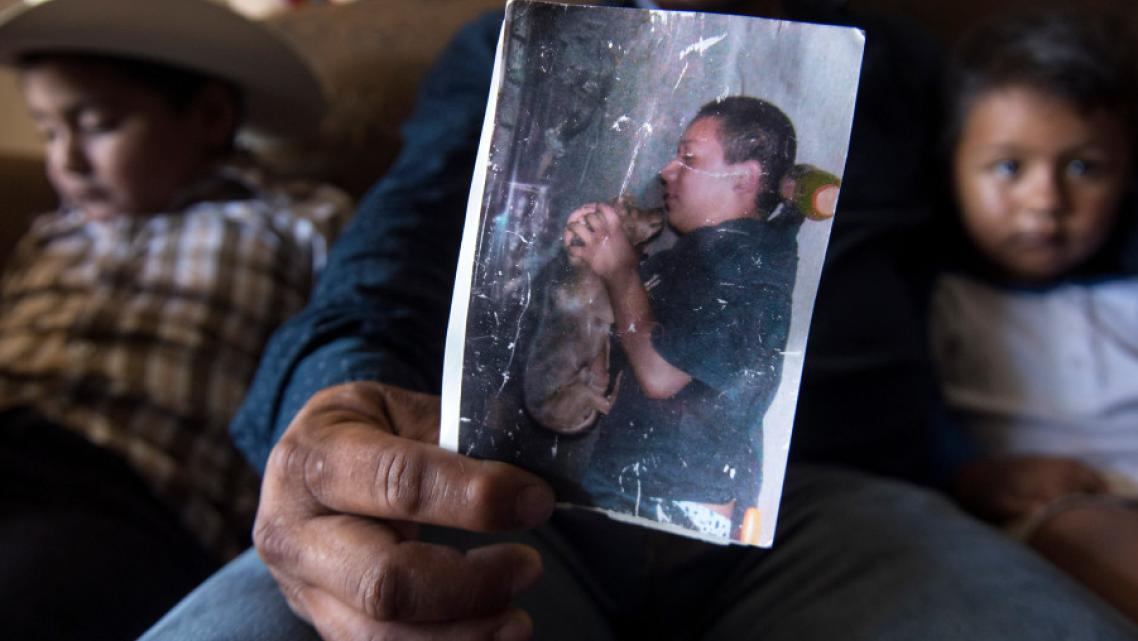 Hugo Secundino, 42, holds a weathered picture of his deceased son Angel.