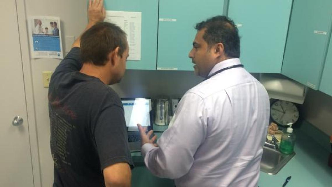 Dr. Ajoy Kumar, right, goes over a patient's blood tests at the St. Petersburg Free Clinic. Julio Ochoa / WUSF Public Media