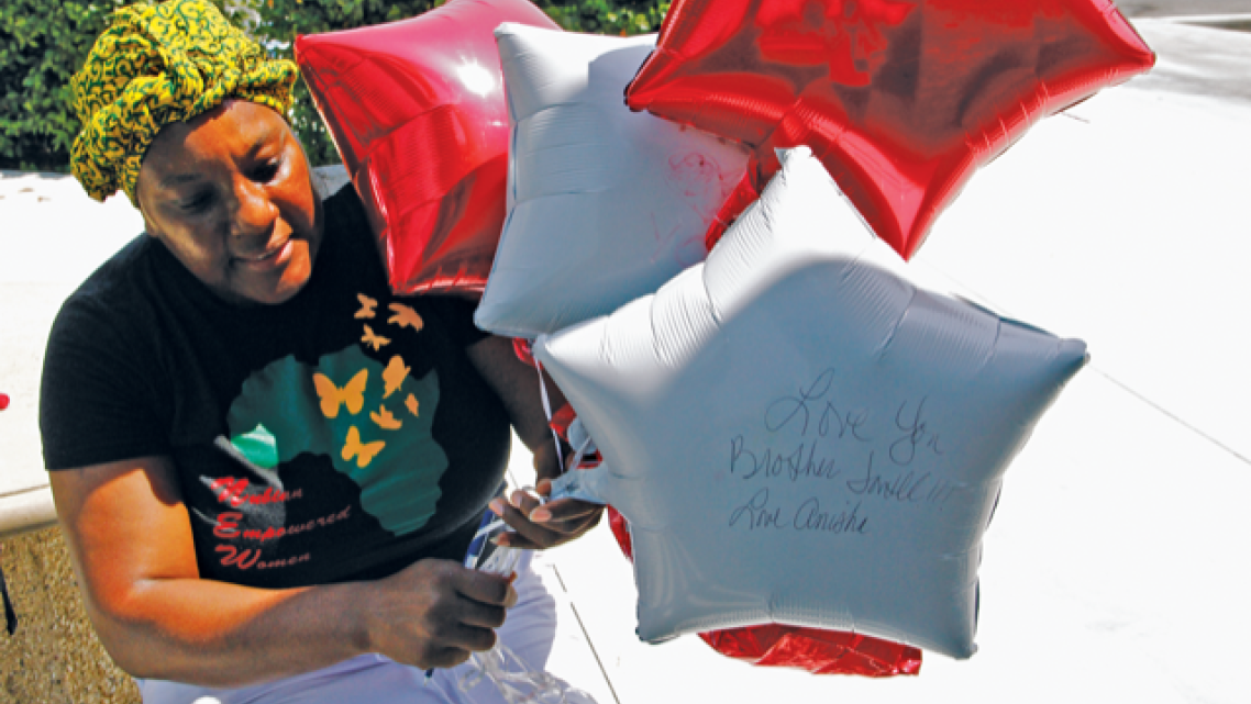 Anyka Harris holds balloons with messages from her and her family for her son Jontell Reedom, who suffered from schiz