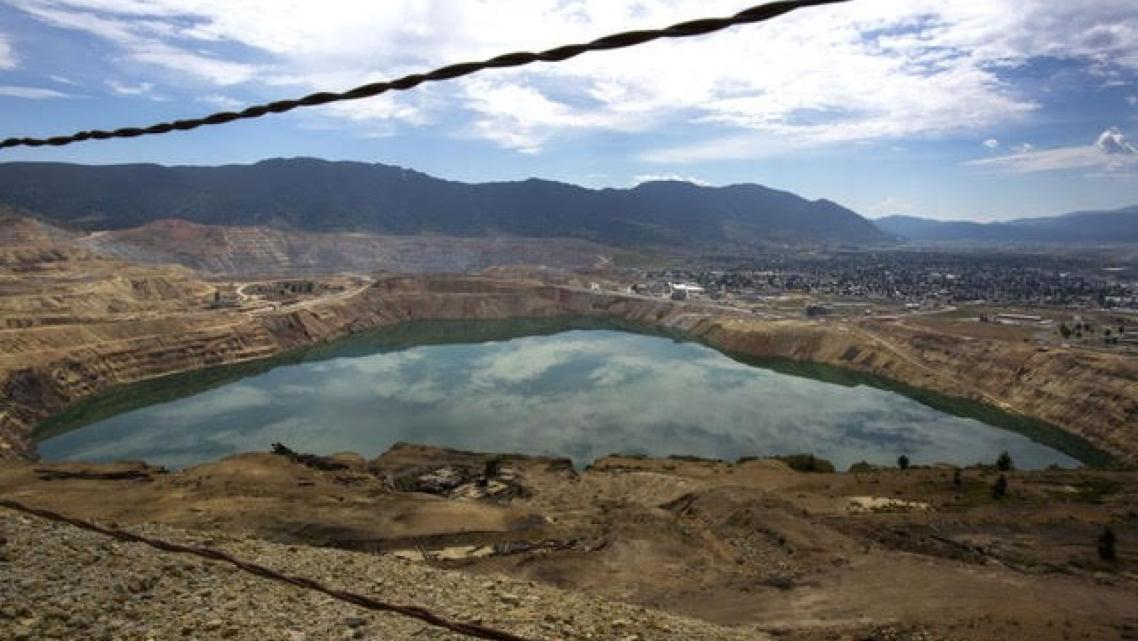 The toxic Berkeley Pit, shown here with the city of Butte in the background, is part of the largest Superfund site in the United