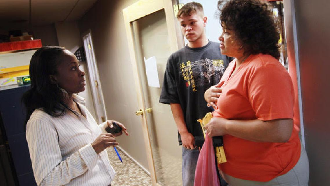 A social worker talks with a mother about signing up her son for food steps in Fort Lauderdale, Florida.