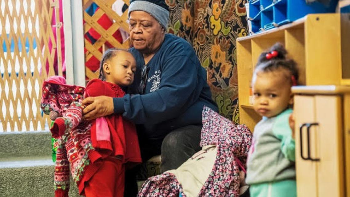 Evelyn West, great grandmother of Kee'Mayah West, 2nd grader, of North Braddock, Pa., dresses children at Great Start Day Care i