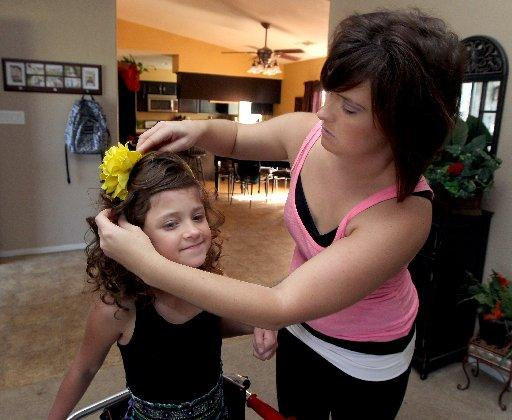 Jillian Lugo fixes her daughter, Jayden's, hair for a picture. The 10-year-old girl has spent most of her life with valley fever and the complications it has caused. She contracted the fungal disease that spread to her brain when she was 2-months-old.