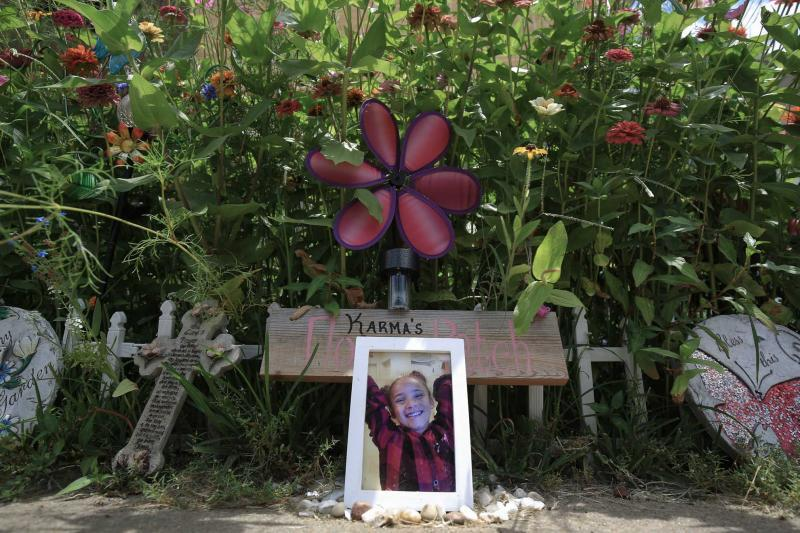 A photo of Karma Wezowicz sits in front of a buttefly garden that Karma and her grandmother, Brenda Wezowicz, had planned together before the 7-year-old was accidentally shot in late February 2017. She died a few days later, and the garden grows in her memory.