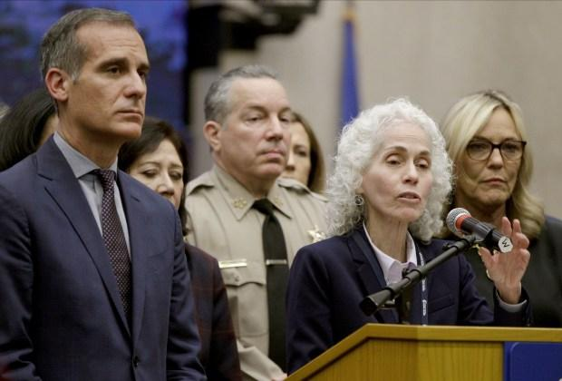 Los Angeles County Public Health Director Barbara Ferrer, at podium, speaks at a news conference with Los Angeles Mayor Eric Garcetti, left, in Los Angeles. (AP Photo/Damian Dovarganes,File)