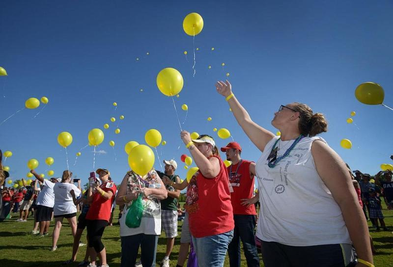 Emily Marie Rogers (right) and her mother, Cindy Lee Rogers of Springdale, join others in releasing balloons during the annual Northwest Arkansas Out of the Darkness Community Walk in 2016 at Orchards Park in Bentonville. The balloons were released in memory of loved ones who died by suicide. (NWA Democrat-Gazette/Ben Goff)