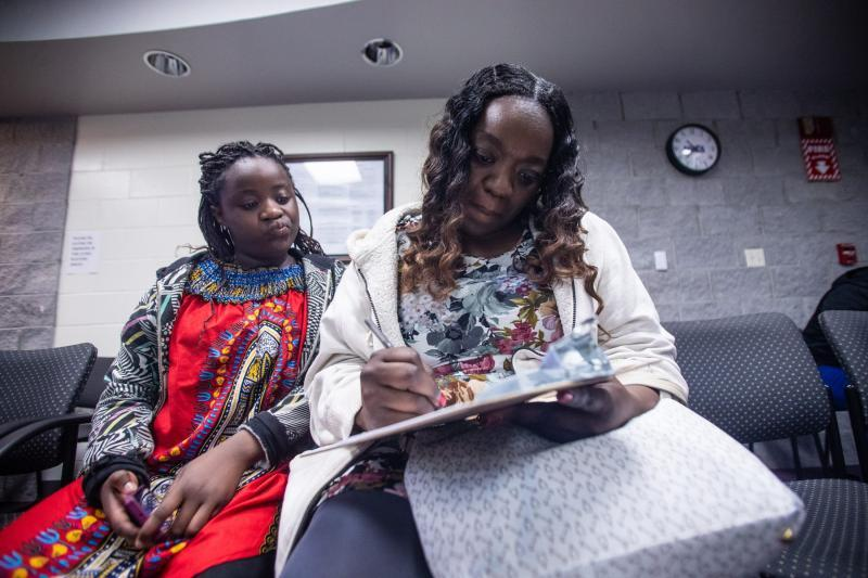 """Kisha Simms, 38, fills out paperwork before a dentist appointment for her 11-year-old daughter Deitra """"DeeDee"""" Jackson at Neighborhood Medical Center. ALICIA DEVINE/TALLAHASSEE DEMOCRAT"""