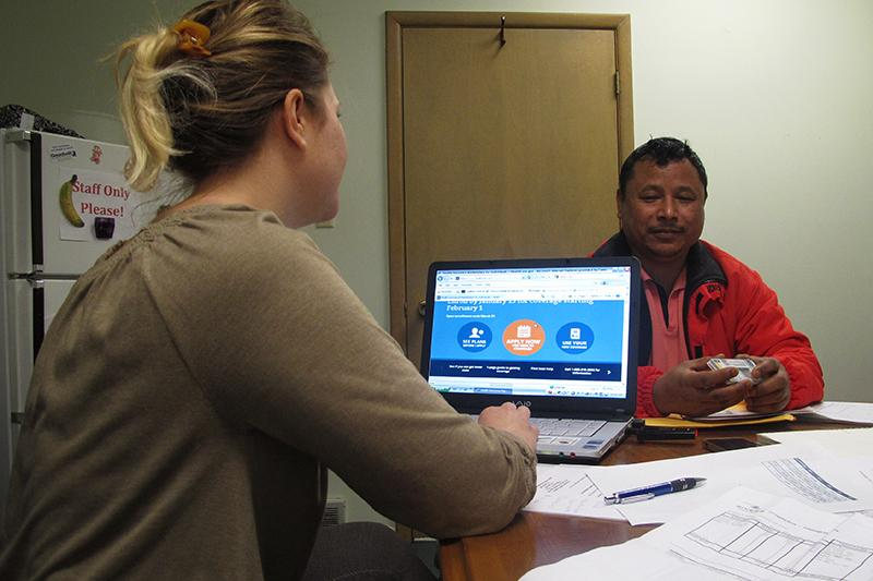 Birkha Tamang, a Bhutanese refugee, hopes to find an affordable health care plan. Assisting him is health navigator Leslie Bachurski of the Consumer Health Coalition.