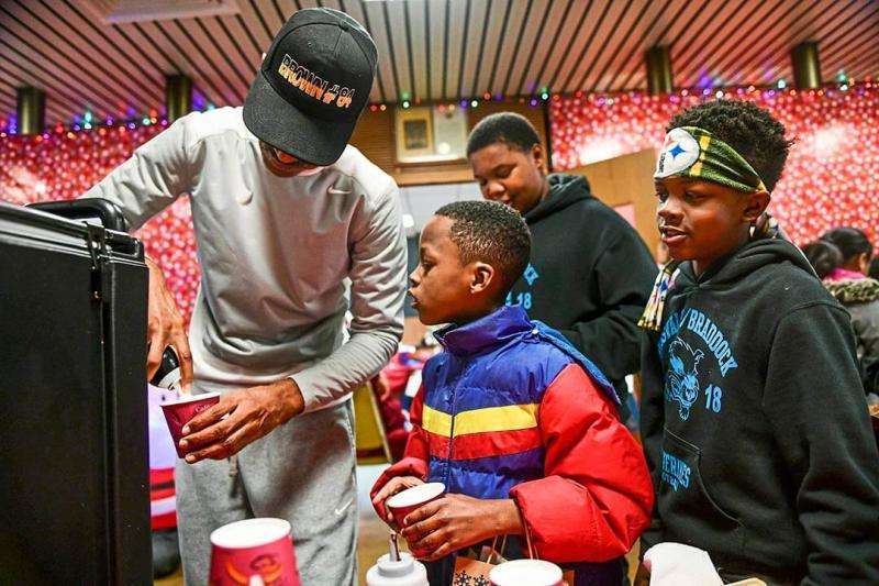 Demont Coleman, former mayor of Rankin, left, puts whipped cream on a hot chocolate as Eric Ramsey, center, and Tyshawn Champine, right, both of Rankin, look on during the Rankin Borough Holiday Night, Dec. 12, in the borough building.