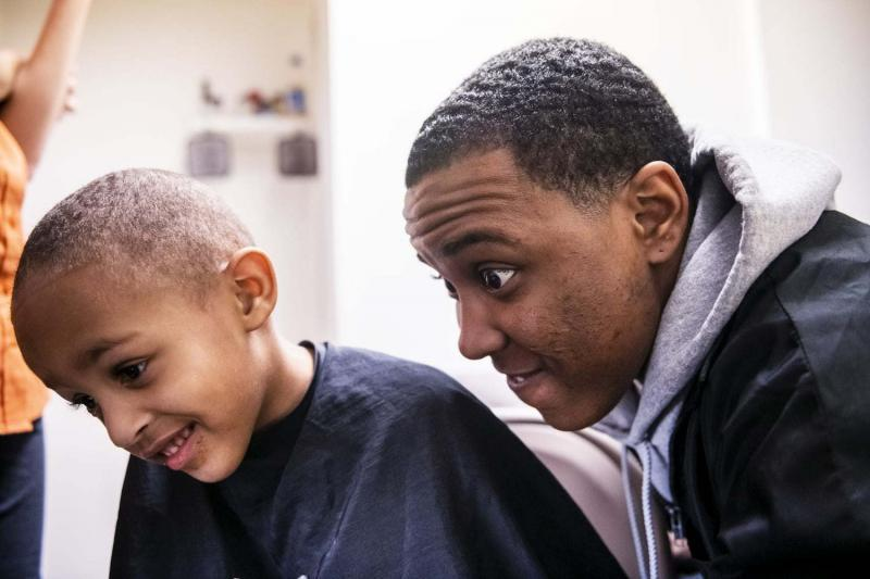Amauri Ray, 3, left, and his godfather Mark Pence smile as they check out Amauri's new haircut in a mirror, Wednesday, Feb. 13, 2019, in Louisville, Ky.