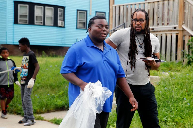 Special projects reporter James E. Causey talks with Marshawn Dixon, 19, who has been in the urban gardening program for years. Dixon said cleaning up his neighborhood gives him a sense of pride.
