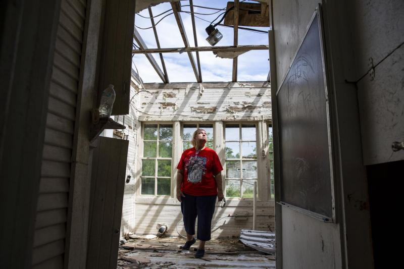 While revisiting her wrecked Bayside home, Sabine Wiegand stands in the foyer and looks up through the hole in her roof for a portrait. Town officials said about 50 homes were destroyed in the storm, driving an unknown number away permanently.