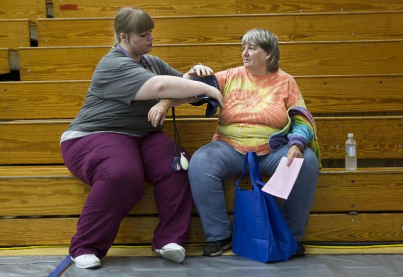 Nursing student volunteer Chelsey Lewis of Jonesville retakes a blood pressure reading for Cheryl Howe, who lives on a farm near Jonesville. Howe was waiting to have teeth pulled but was not permitted to enter the dental clinic until her pressure fell. She was diagnosed with hypertension a few months earlier when she went to an emergency room for abnormal bleeding and cramping, but she could not afford to go to a primary care clinic to get a prescription.