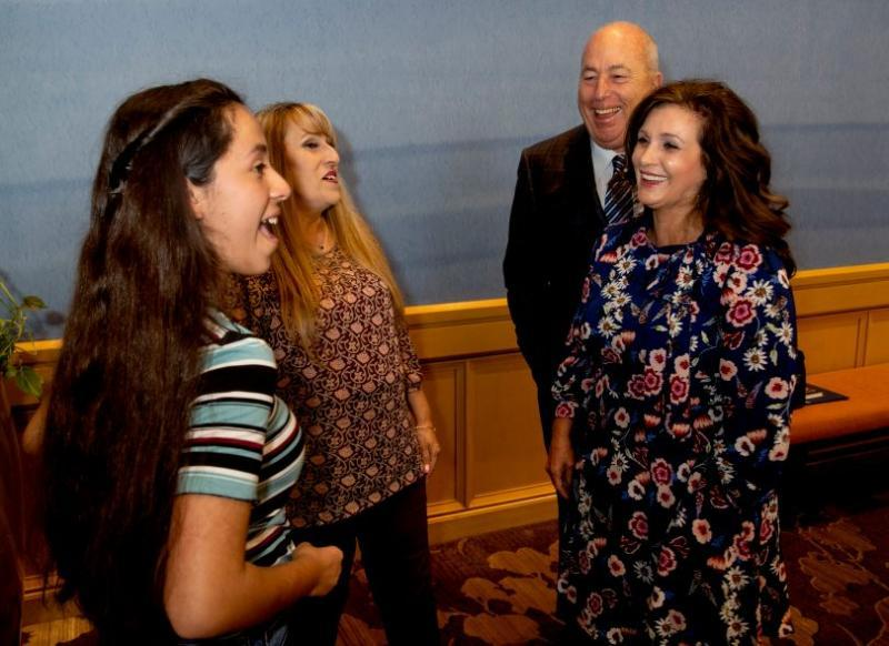 Elainna Estrada, 14 and her mom Yvette, left, talk with Toni and John Ginger at the Ambassador Luncheon for the Orangewood Foundation in Costa Mesa, CA on Friday, November 2, 2018. The Gingers received the General William Lyon Crystal Vision Philanthropy Award for their more than 20 years of foster parenting. Elainna was one of the kids they fostered from her birth until about 3 months old. (Photo by Paul Bersebach, Orange County Register/SCNG)