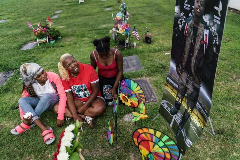 Brigitte Green is consoled at the burial site for her son, Monyae.