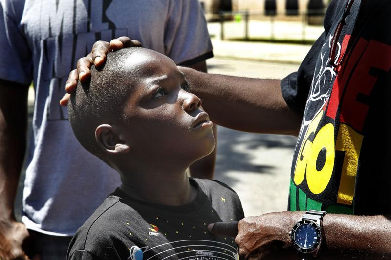 """Andre Lee Ellis, founder of """"We Got This,"""" gives Nicholas Johnson, 9, a rebuke on a Saturday in June. Ellis is known for his stern approach, but at the same time often tells the boys they are special and he loves them – words he says they don't hear often enough."""